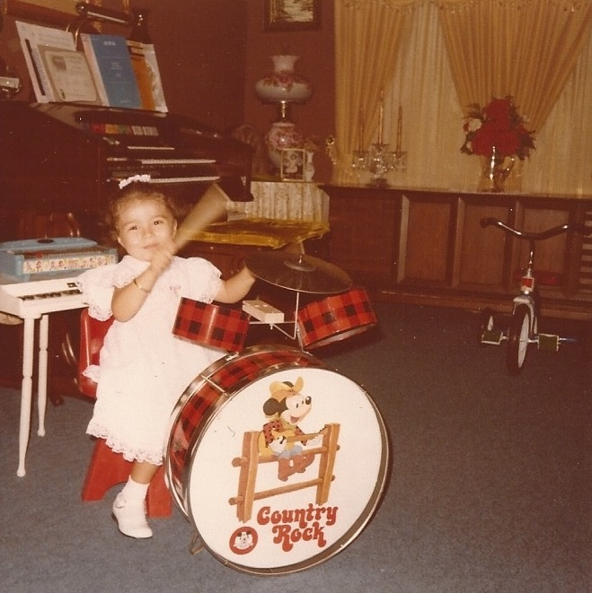 Angie playing the drums at age 3