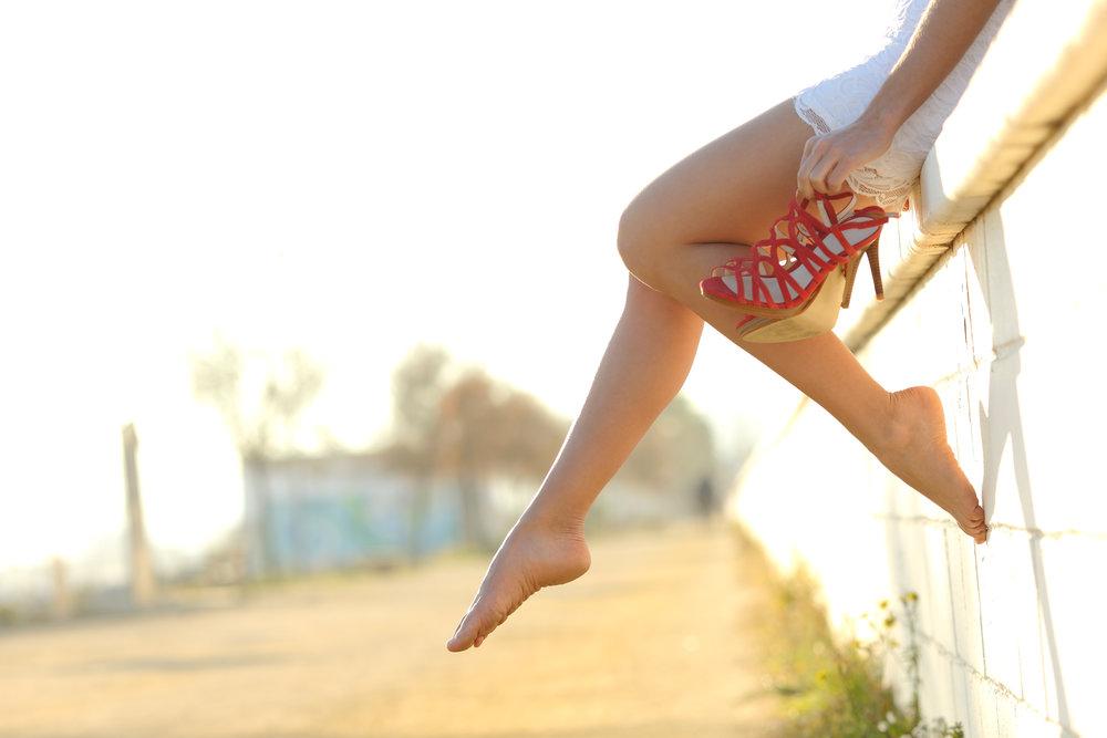 Woman legs silhouette with heels hanging of her hands.jpg