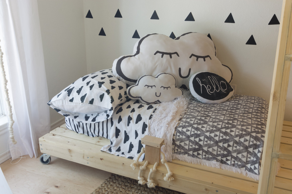 Gender neutral scandinavian style kids room in this warm, cozy, Scandinavian inspired home in Texas with wooden floors and white walls.