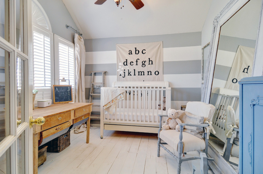 Pale grey striped walls in the nursery in this warm, cozy, Scandinavian inspired home in Texas with wooden floors and white walls.
