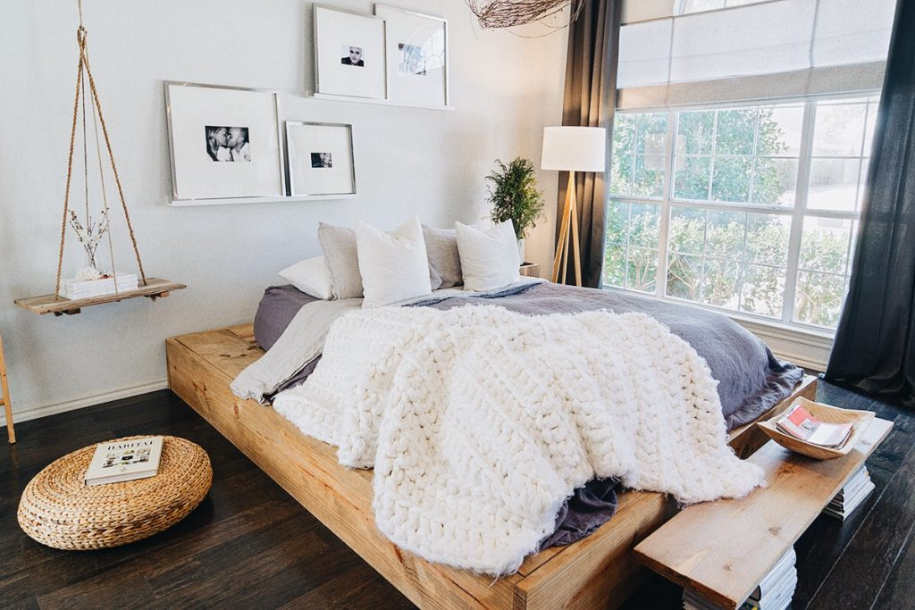 Earthy boho bedroom in this warm, cozy, Scandinavian inspired home in Texas with wooden floors and white walls.