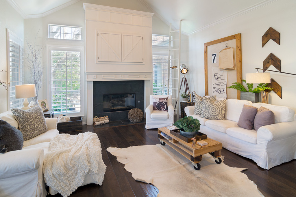 White sofas, comfy throws in this warm, cozy, Scandinavian inspired home in Texas with wooden floors and white walls.