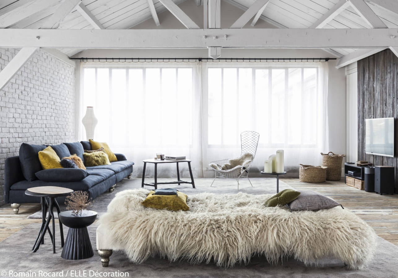 Relaxed boho vibes in this loft with Ikea sofas with Designer Guild, linen covers, sheepskins and the famous Harry Bertoia Bird chair