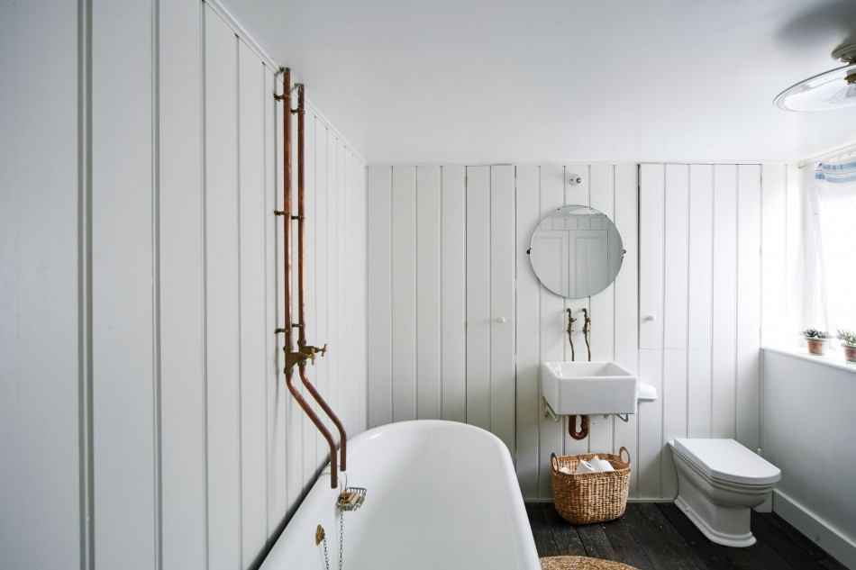 The white tongue and groove bathroom is notable for the bespoke fittings formed from copper piping