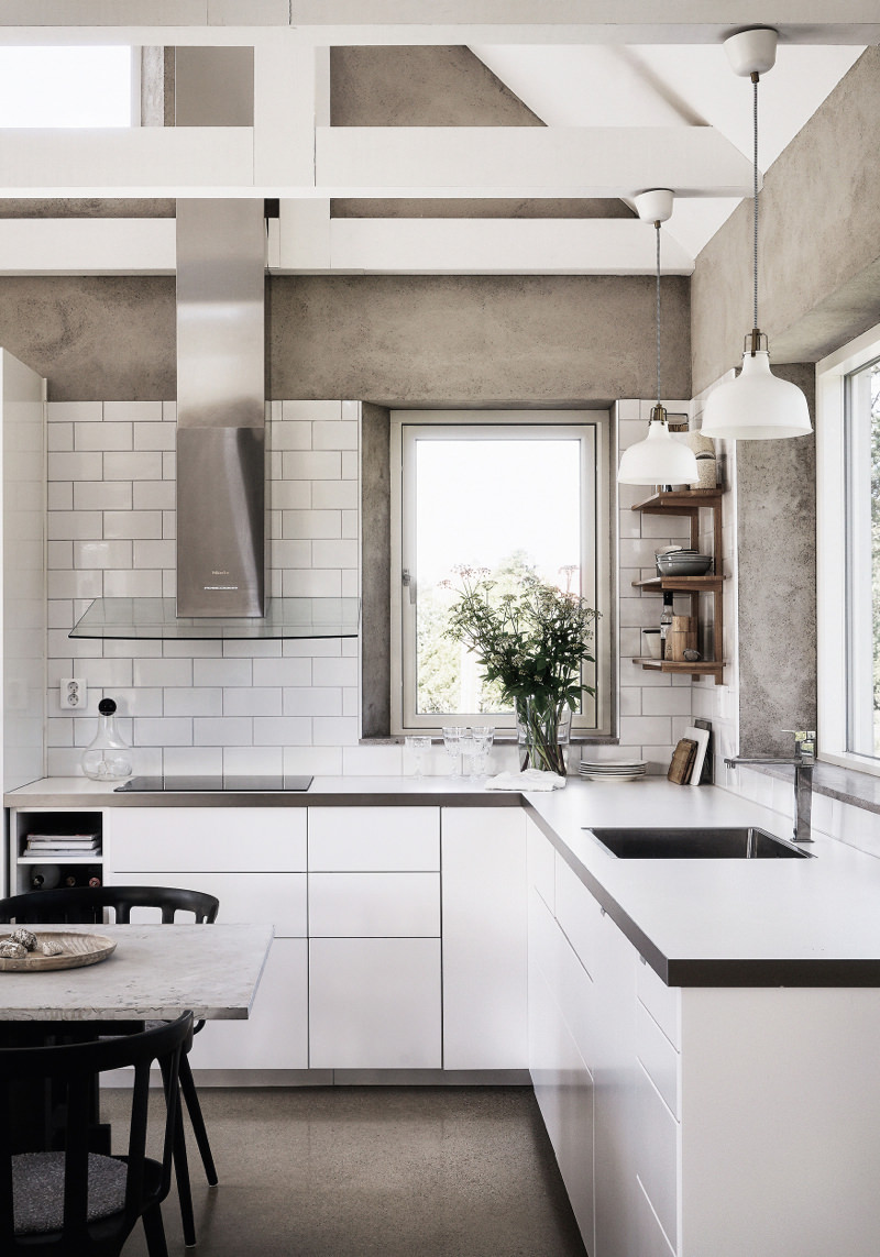 White minimalist modern kitchen has been given texture and interest with a clever choice of bare concrete walls