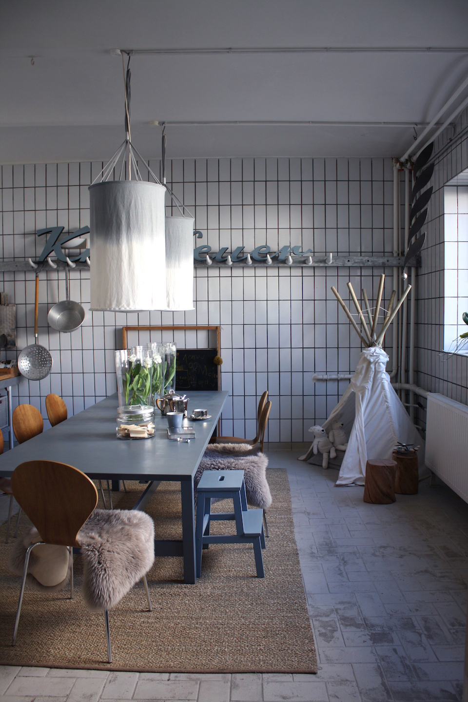 A mix of weathered barn wood and handmade textiles by Sabine herself have transformed this industrial space into a relaxed and tranquil family home.
