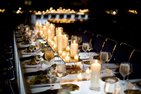 high-low-white-candles-arranged-down-middle-of-wedding-reception-tables