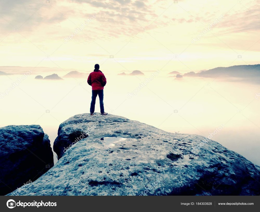 man on mountain above clouds.jpg