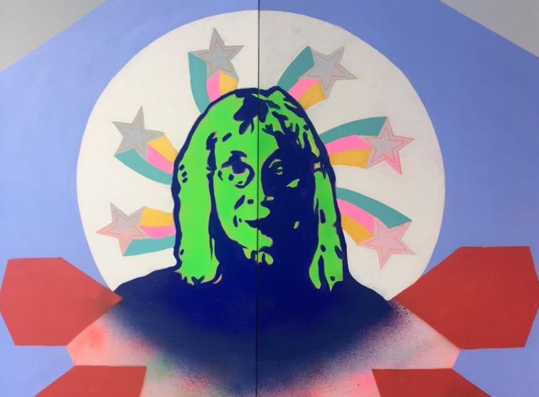 Suzanne Osten i utställningen Kvarterets Kvinnor. Muralmålning av Saadia Hussain.