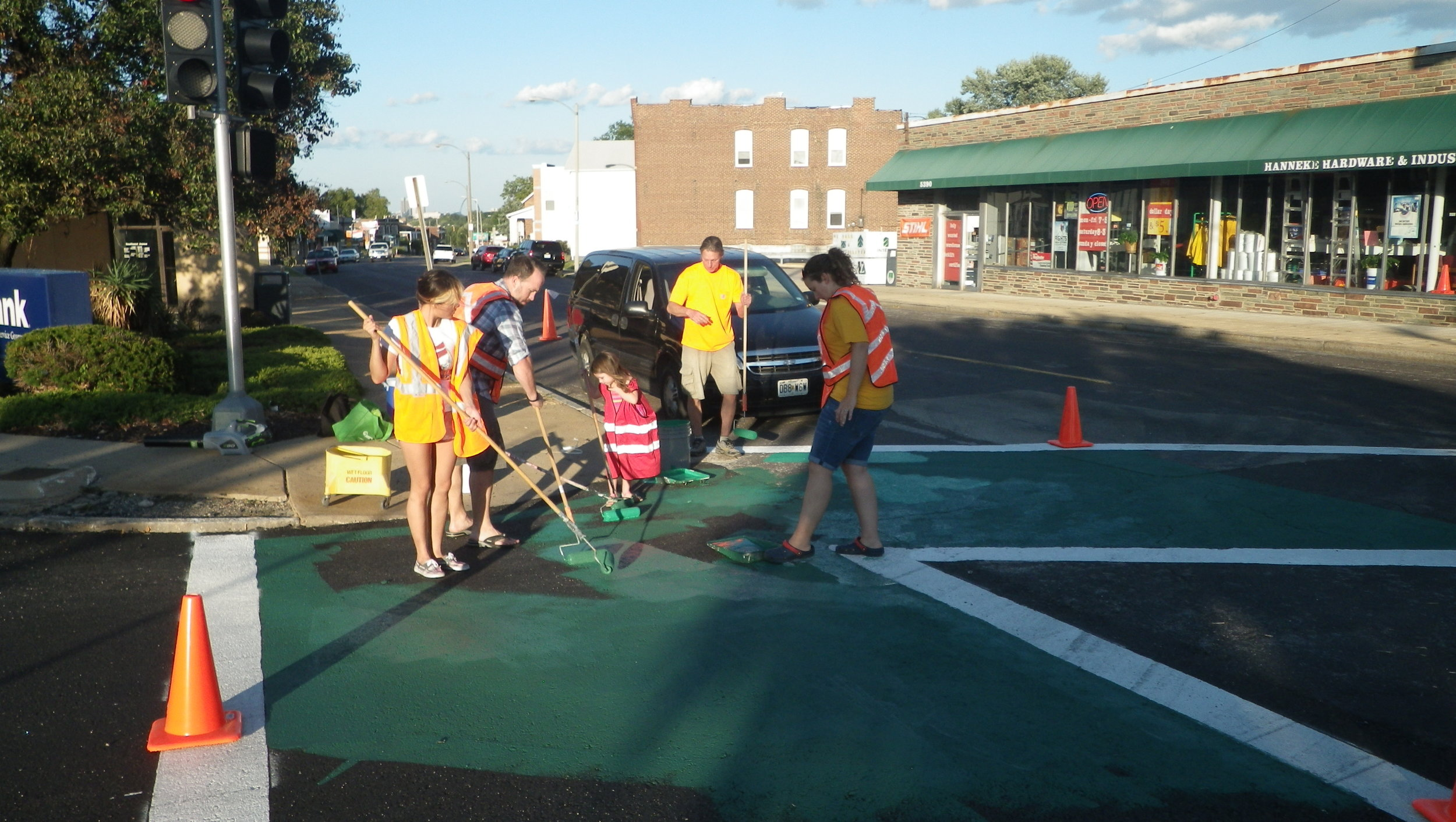 Volunteers paint the crosswalks at Macklind and Southwest Ave in Southwest Garden neighborhood as part of the neighborhood beautification projects.