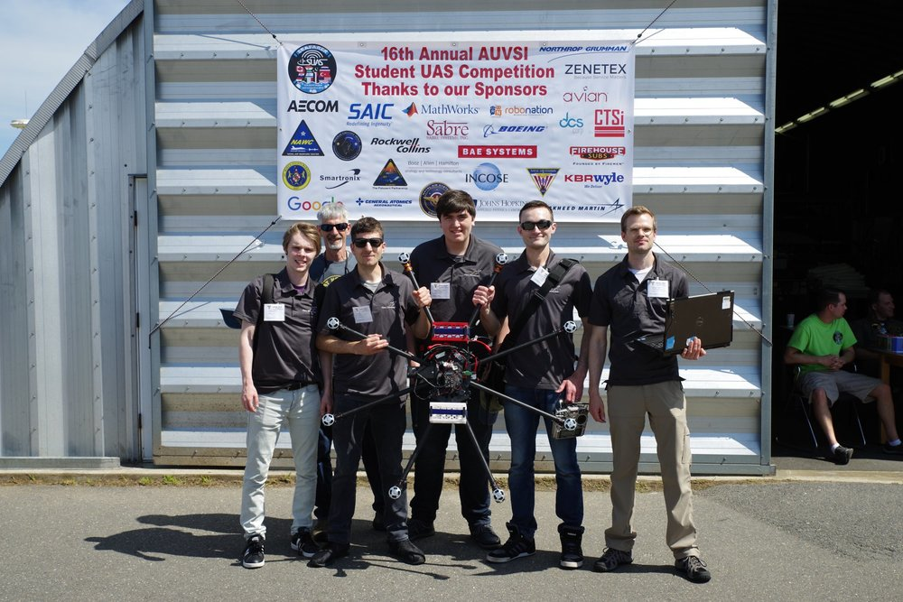 Six people holding a large unmanned drone aircraft.