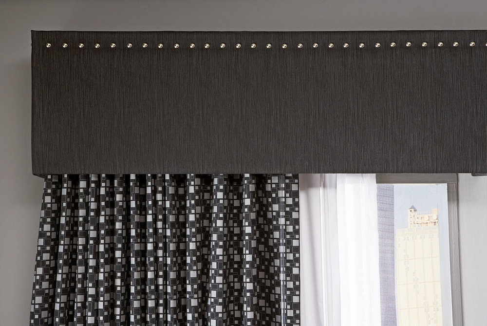 Top Treatments - Mask your window treatment hardware with elegant wood and upholstered solutions.
