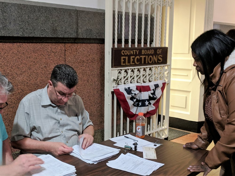 Carla Cain (right) submits petitions with almost 4,100 signatures at the County Board of Elections