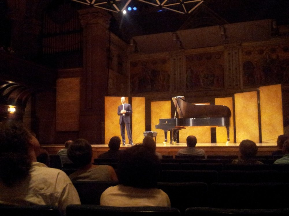 Ilya Itin announces a Rachmaninov encore after a recital of Debussy and Liszt