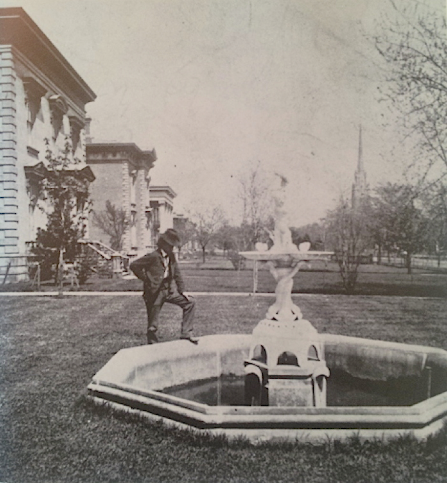 Fountains and sculptures were a common sight in front lawns--this scene is set in 1870.
