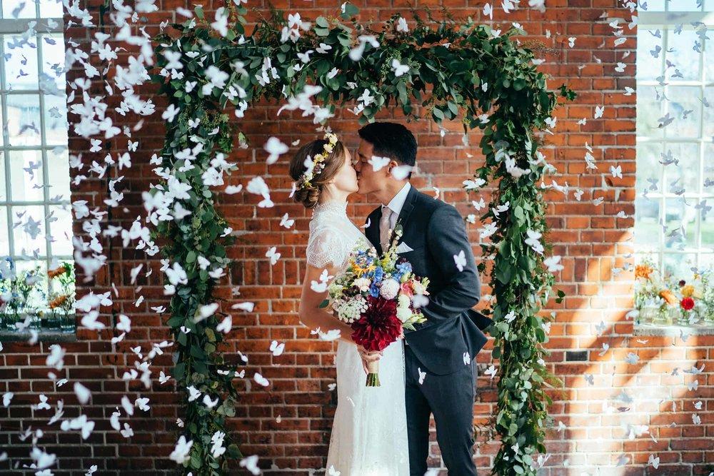 brudepar-kysser-med-konfetti-bryllupsfotograf-københavn.jpg