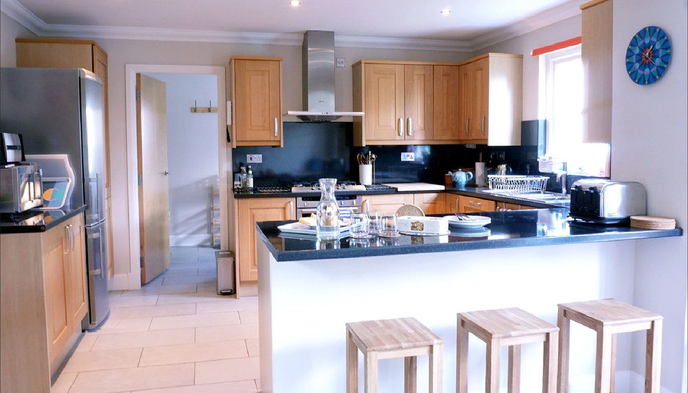 Kitchen with breakfast bar and utility room beyond
