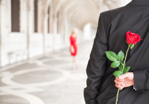 Man waiting for his date with red rose behind his back