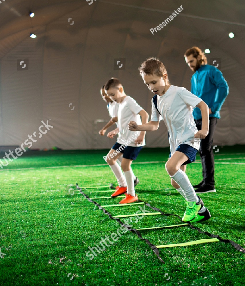 stock-photo-youthful-kids-in-uniform-exercising-during-football-training-on-green-lawn-1032938152.jpg