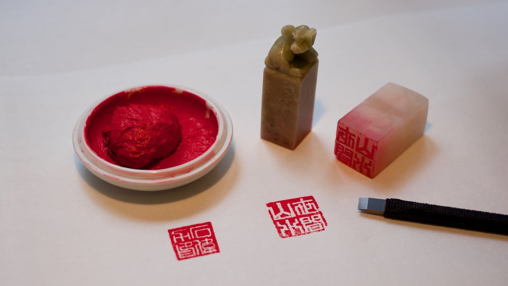 Two seals and their imprints, together with red ink and a carving knife.