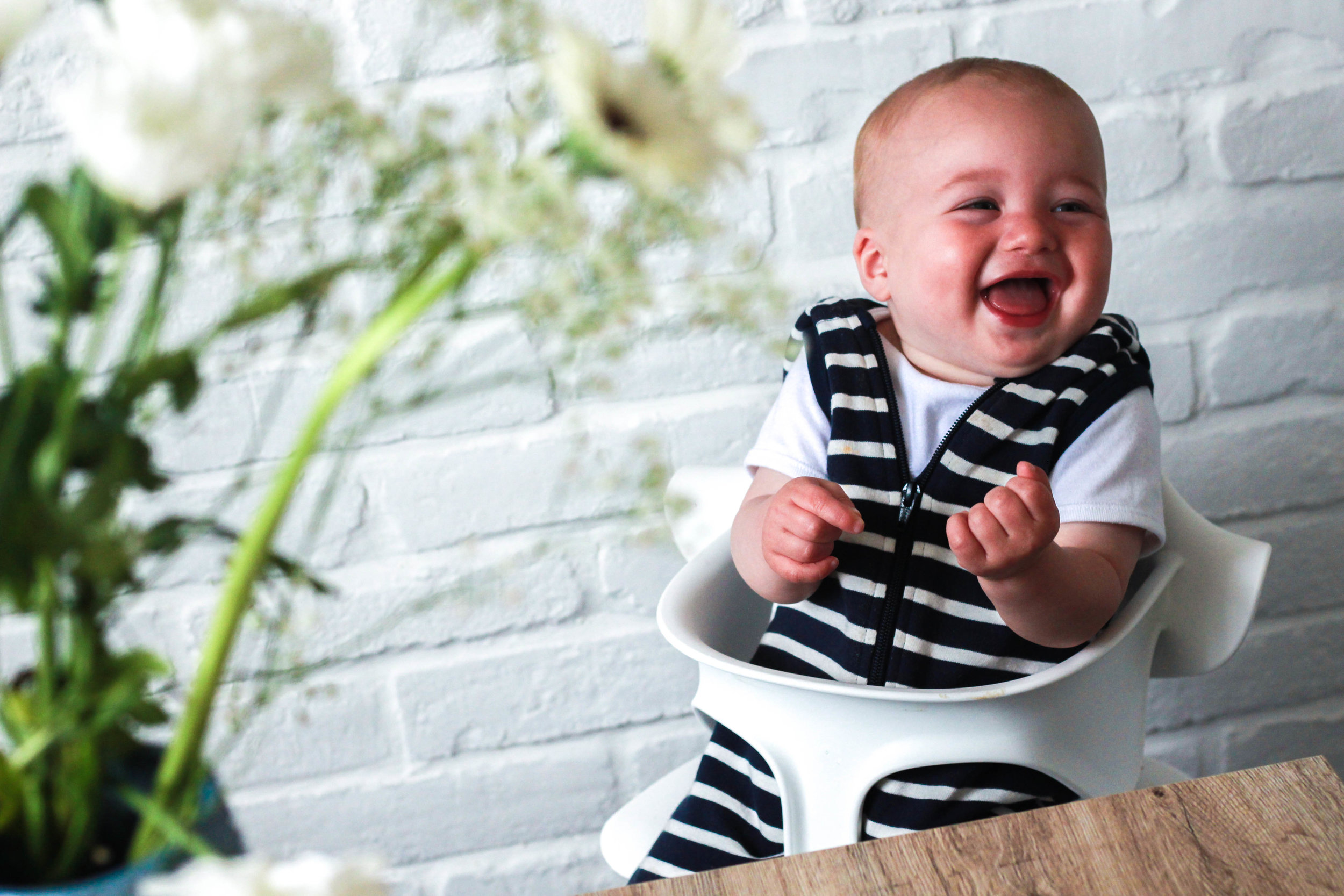 life lessons toddlers teach Baby laughing in noms high chair at table with plants