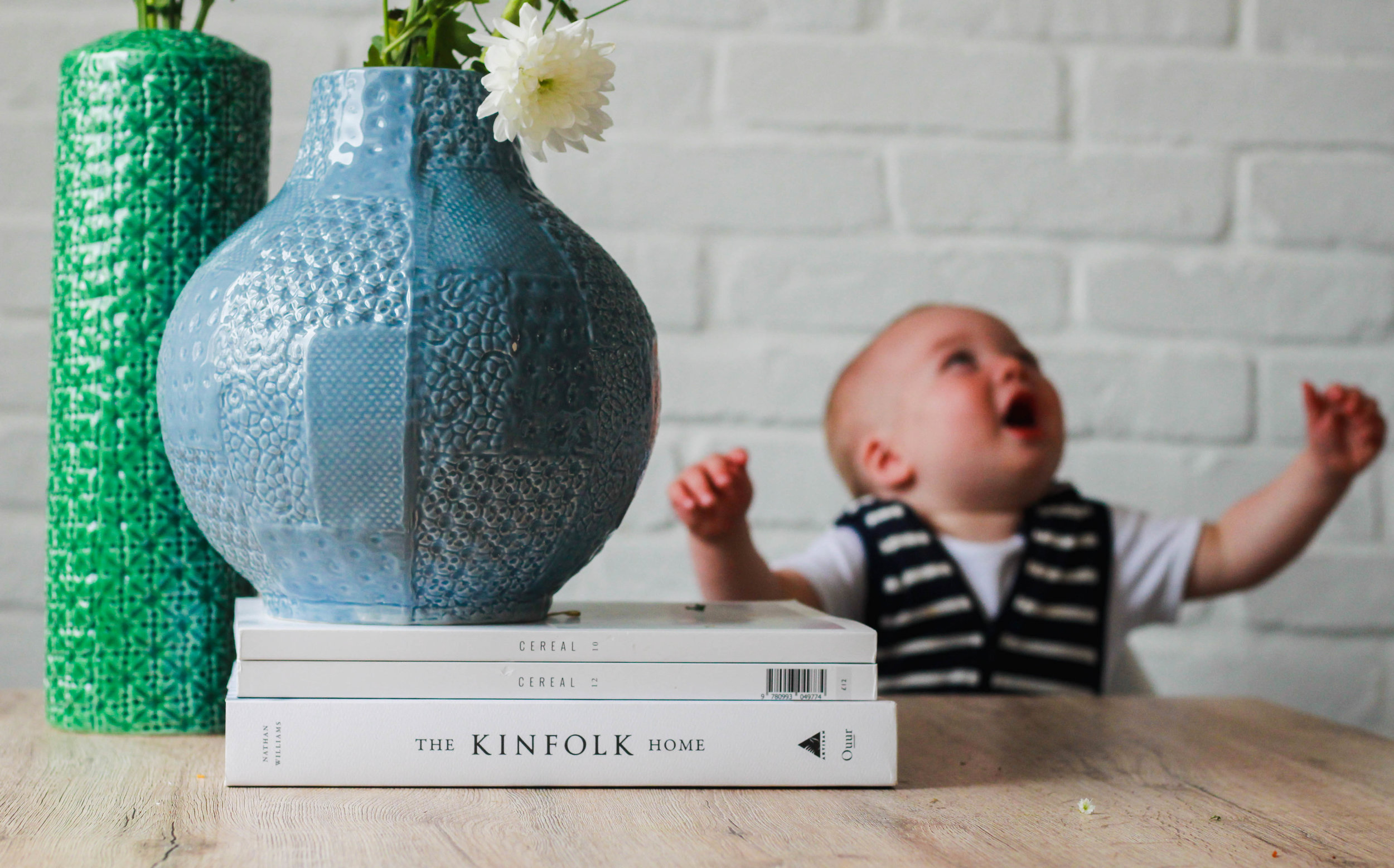 Baby laughing in noms high chair at table with plants