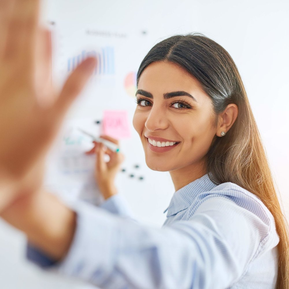 high-fiving-coworkers-at-white-board-PL7ADRY.jpg