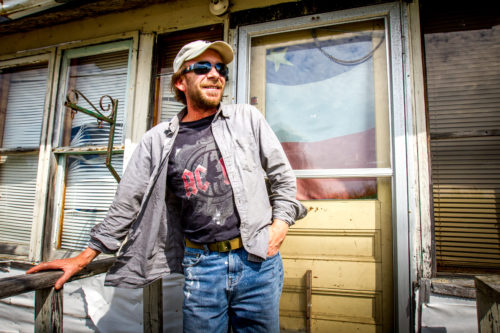 """Rodney Kail poses in front of the house in which he has resided in Acadieville, NB, for the past 40 years. """"There's no work here, but I can't bring myself to leave,"""" said Kail, who has consistently travelled to either Moncton or Miramichi for work."""