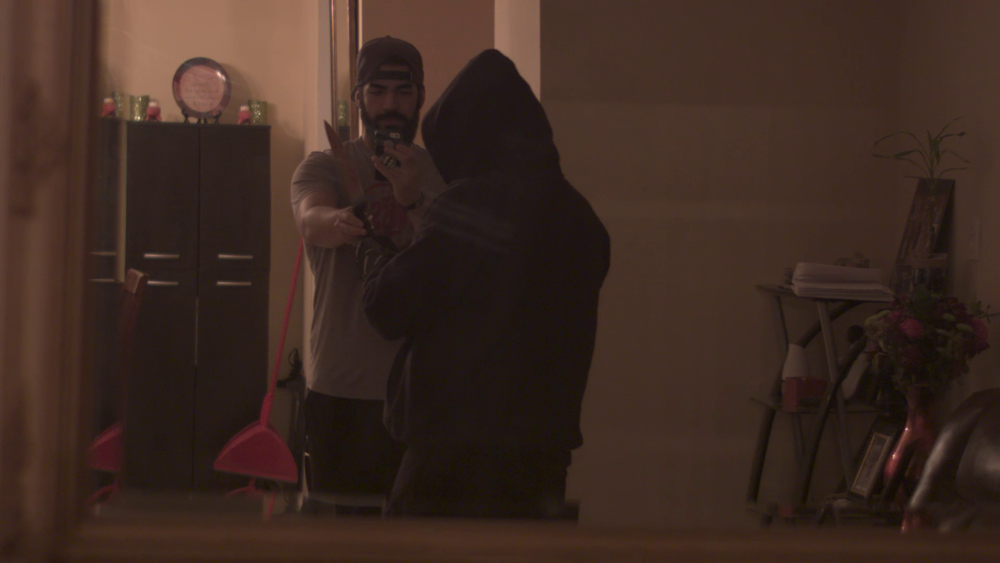 Actor and Production Coordinator, Michael Cards, giving a prop knife to the killer right before filming a scene.