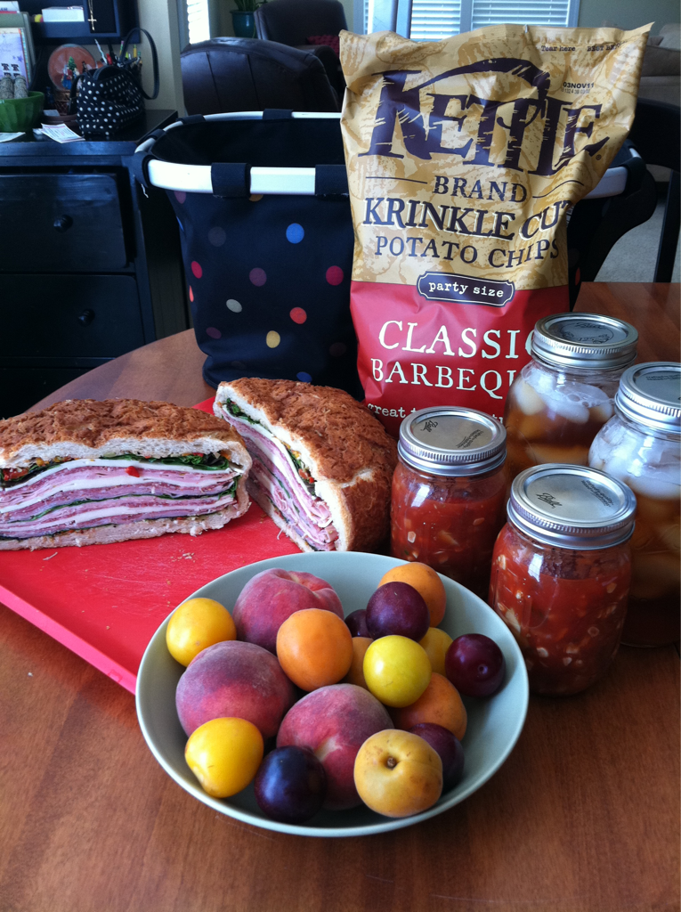 My sister-in-law and niece are visiting our area from San Francisco this week. They are spending the afternoon with us at the pool. So I have made a lunch spread that can be eaten pool side. On the menu is a muffuletta, chunky gazpacho, sun tea, chips, and an assortment of fruit we got at the farmer's market this morning. I love packing the gazpacho and sun tea in glass canning jars because it makes it so portable and eco friendly.