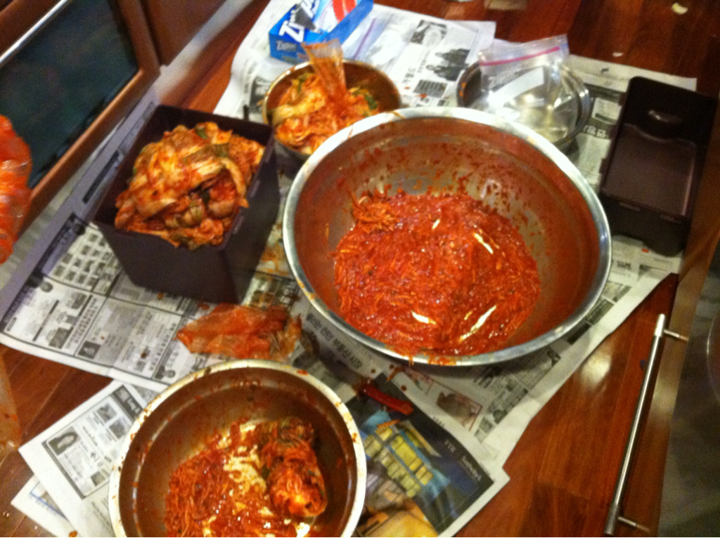 Kimchi Day Next week we take our long drive to Boulder, Colorado for our big family move. Last Friday we moved everything we owned into a giant pod to be shipped across country. This week we are staying with my parents in Bethesda, Maryland where I grew up. It has been nice to be here with my kids and enjoying the benefits of living in this suburbaurban (this is a word my son uses to describe the neighborhood) area. The best was that was able to help my mom make her amazing kimchi. This is a traditional staple food of South Korea. A spicy fermented cabbage that you eat at practically every meal. My mom is known for her kimchi. I have made this dish a number of times but never comes out the way it should. Tasty but never ever as good as my mom's. Well she said one of the secrets is that she gets her red pepper flakes shipped her Korea through her sister. She actually purchases Korean red peppers from local farms that grow them organically. Then she sun dries them and then gets them ground. Wow! The time and commitment really shows through in the taste and color. It was amazing to sit on the kitchen floor, mixing all the ingredients by hand and individually covering the cabbage leaves with the red pepper paste mixture. We had so much fun talking and making this wonderful dish. It tasted amazing and will be even better once it is allowed to ferment. More importantly it was made with pure ingredients and love.