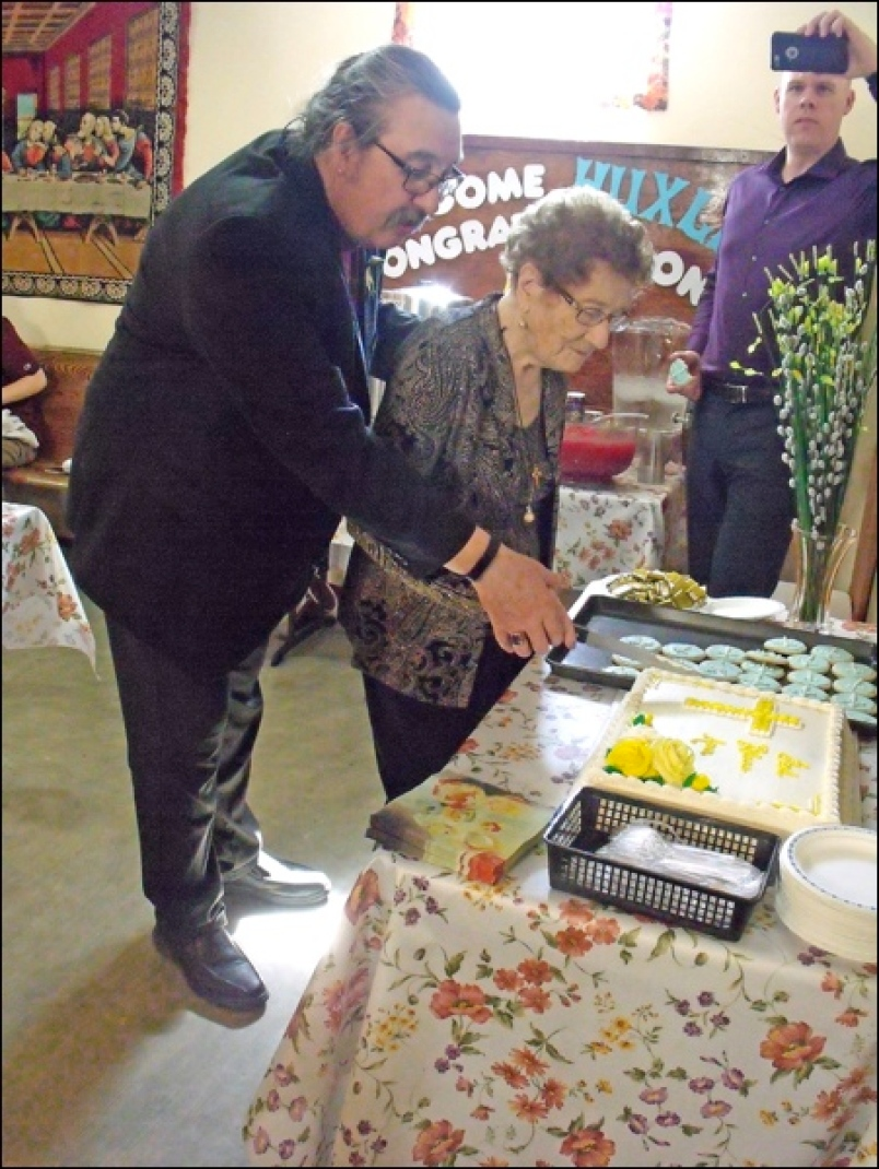 Bishop Harper cutting the special cake with Ann Brand helping.