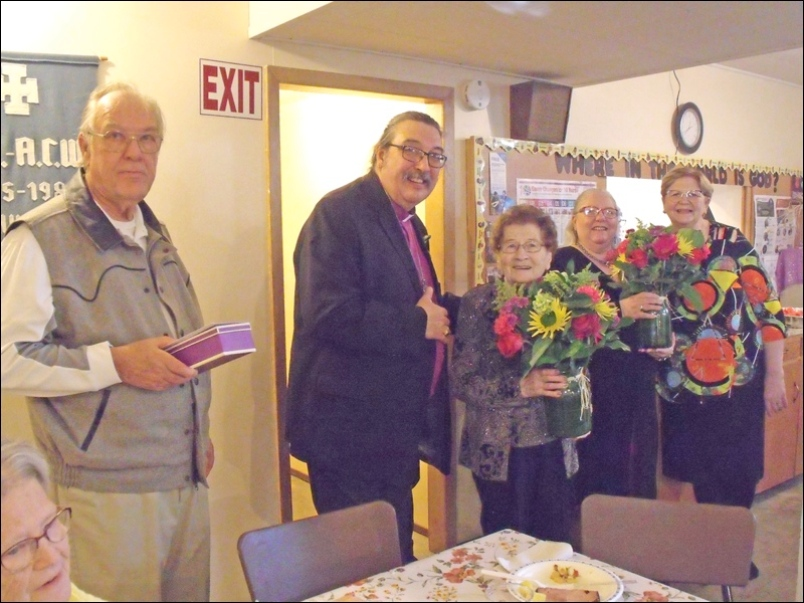 Presentations - Ray Latimer with a wooden cross for Bishop Harper, bouquets of flowers to Ann Brand and Mrs. Tracy Harper.