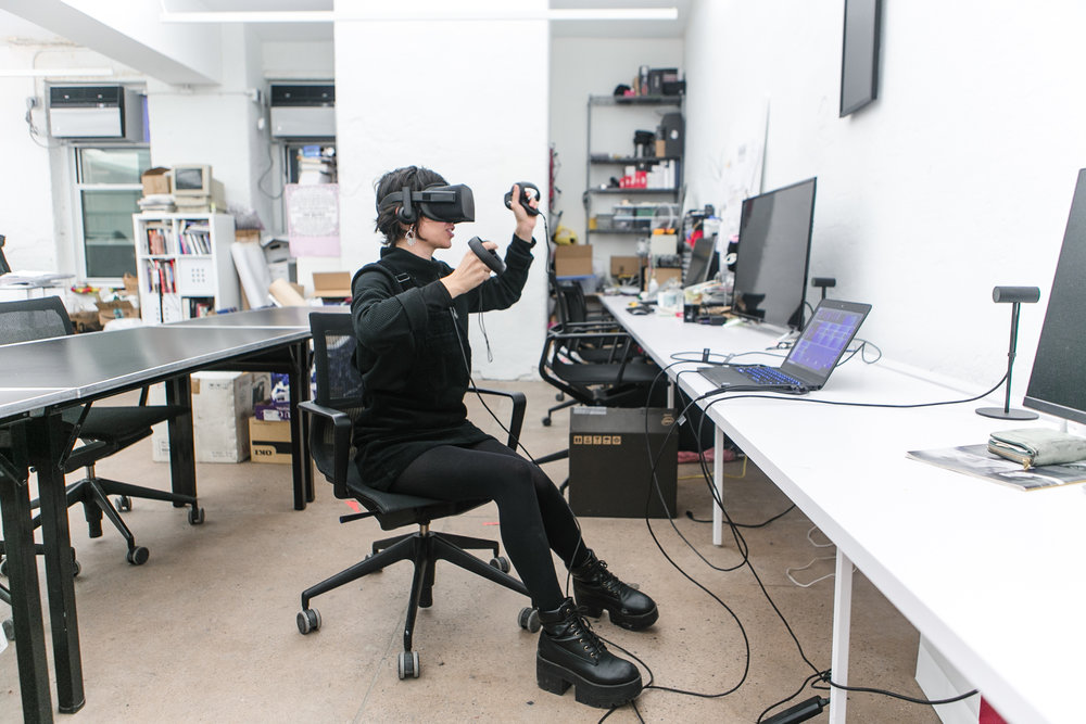 NEW INC member wearing VR goggles