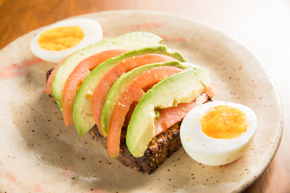 Toast Topped with Avocado and Tomatoes, with a Boiled Egg on the Side