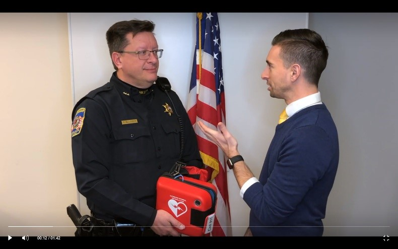 Police Chief Craig Bangert and President Bull discussing the Defibrillator and the fund raising efforts of the Chamber.