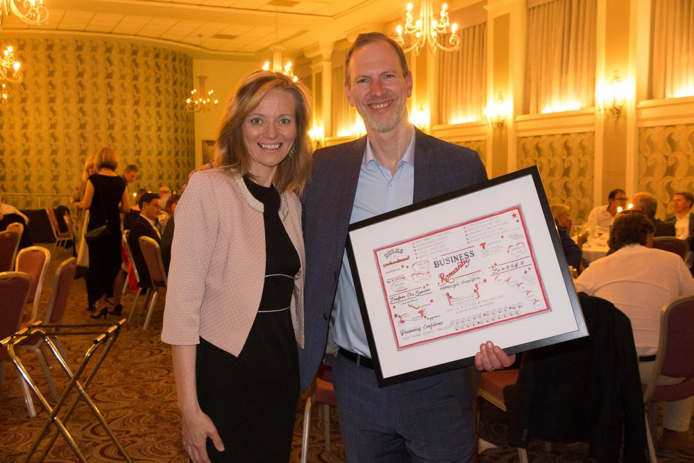 Dani presenting Tim Leberecht (author) with a framed visual synopsis for his book Business Romantic