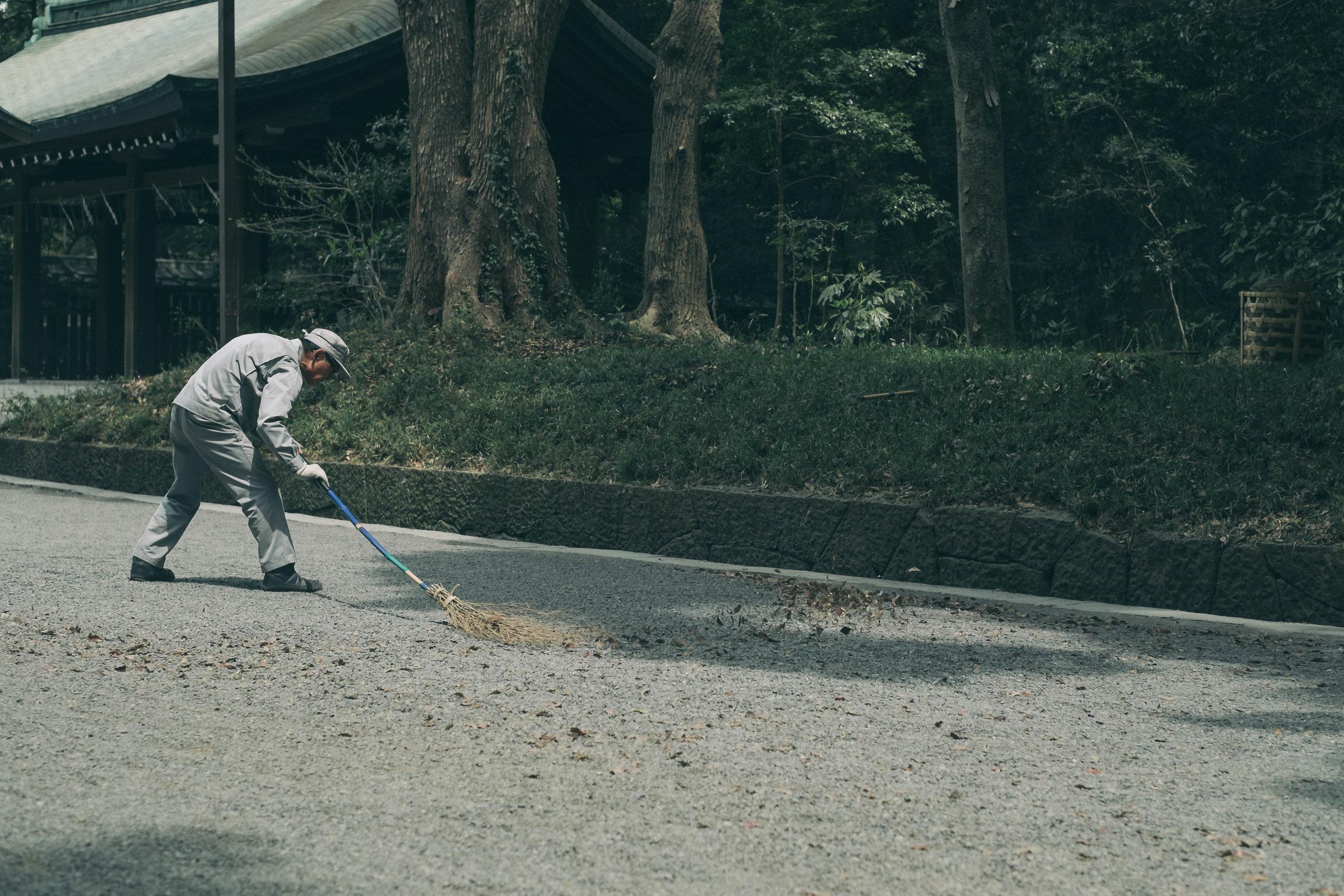 Older gentleman sweeping leaves, Tokyo.