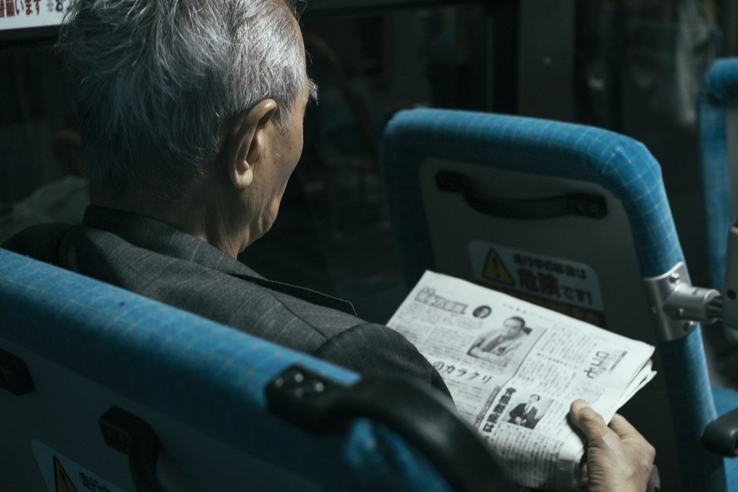 Older gentleman reading the paper in a Kyoto bus.