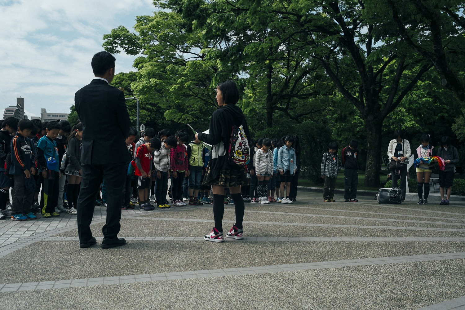 A class of Japanese children bowing before the Children's Peace Monument in Hiroshima.