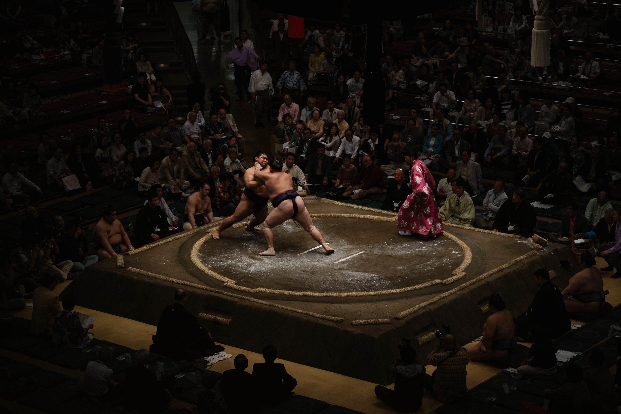 Sumo fighters going at it while the judge watches, Tokyo.