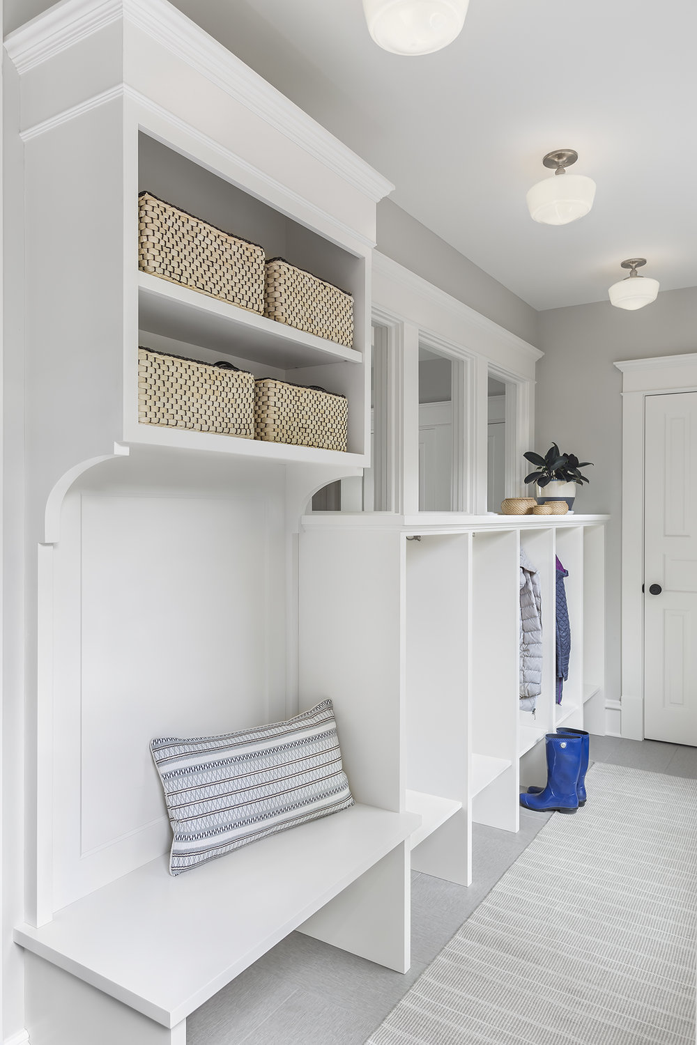 Enclosing the back stoop of the house allowed for a new mudroom space. Individual cubbies for each family member help contain clutter and a heated tile floor keeps the room cozy.