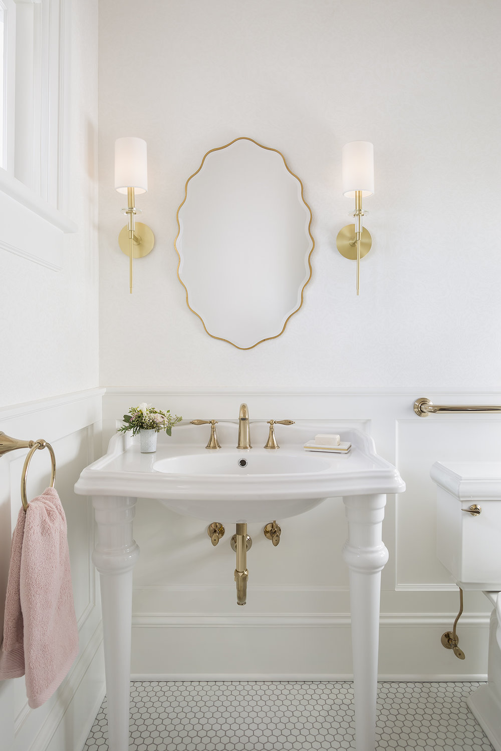 A porcelain console sink paired with a traditional brass widespread faucet contrasts with modern sconces and a whimsical mirror.