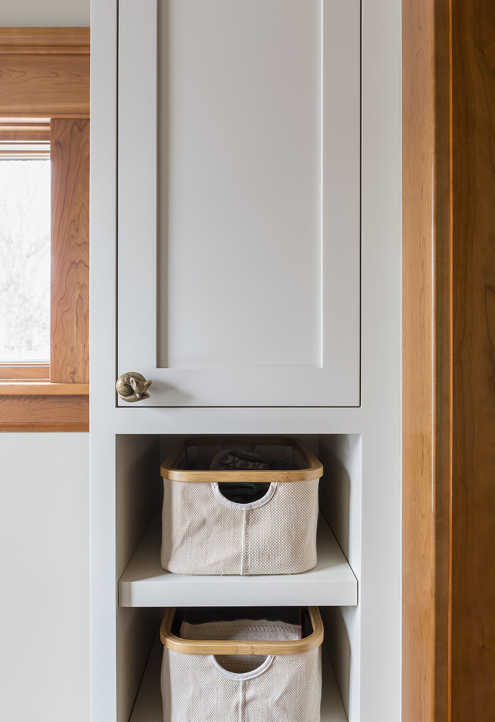 The custom cabinets are painted a subtle khaki color and the natural baskets provide storage. Whimsical hardware adds a playful touch.