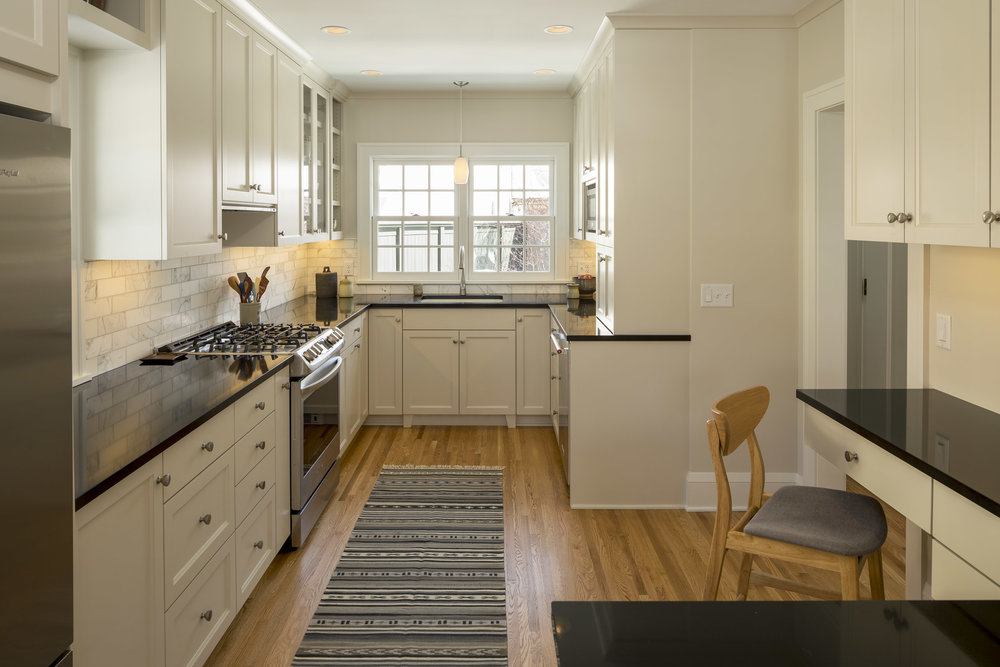 Pale grey cabinets and a reconfigured layout helped open up this kitchen and better connect it to the rest of the home.