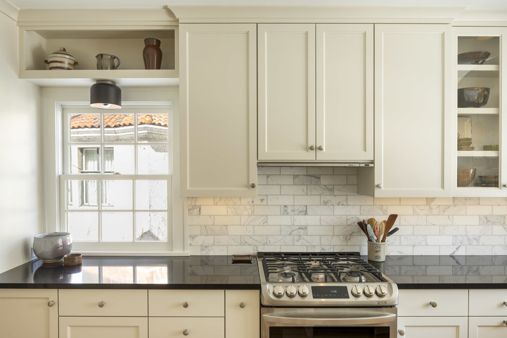 Glass-front cabinetry and open shelves allow the homeowners to display some of their favorite pieces of pottery.
