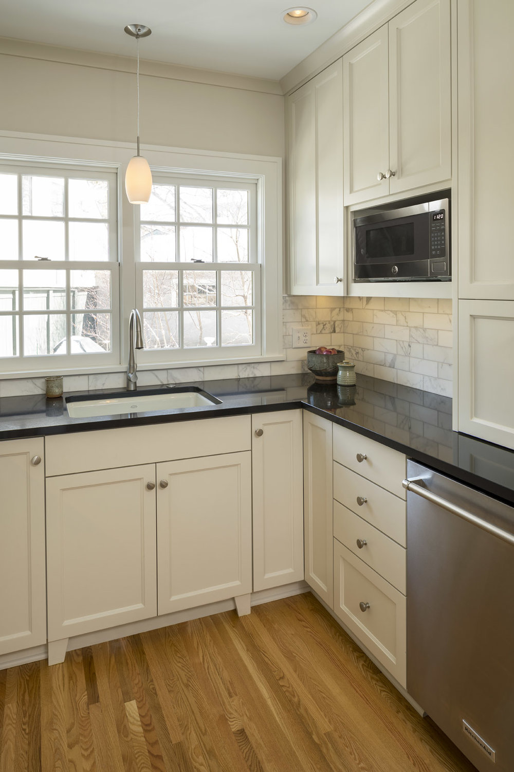 Frameless cabinetry, quartz countertops and a marble-tile backsplash strike just the right balance of old and new.