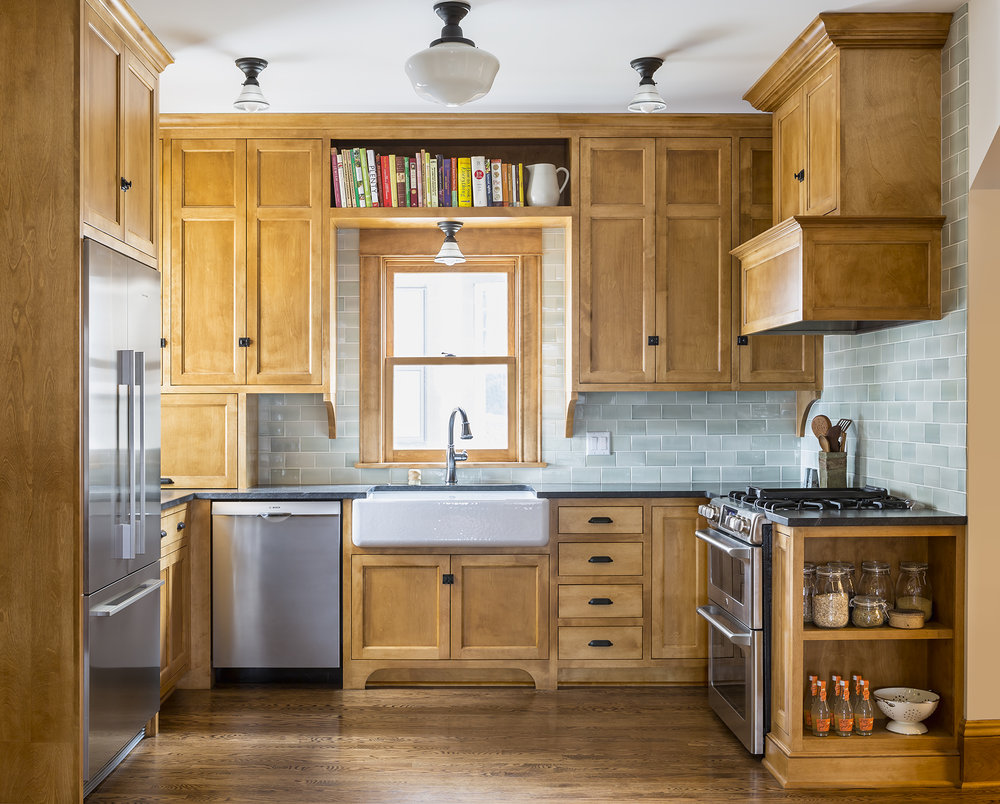 Stained wooden cabinetry and honed-granite countertops, as well as reproduction lighting and hardware contribute to the historic feel the homeowners wanted.