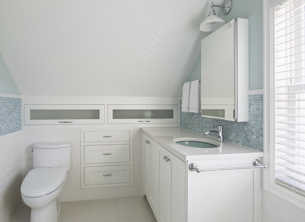 Maximizing storage was a top priority of this project. A custom vanity with integrated electrical and roll-out drawers, a medicine cabinet with interior outlets, and drawers in the previous unused knee-wall area all contribute to meeting this goal.