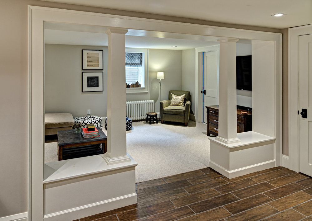 A neutral palette and natural materials such as wood and wool help the basement space feel bright, cozy and welcoming.